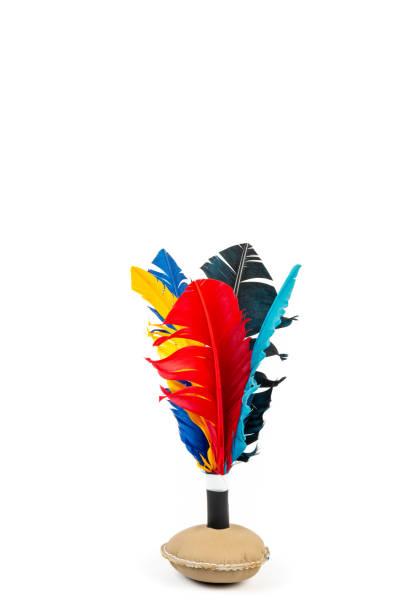 Gros jouet volant à la main avec des plumes colorées sur fond blanc. - Photo