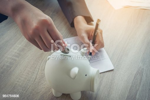 istock Close up of hands business women putting coins into piggy bank. Investment and saving strategy concept. 954754606