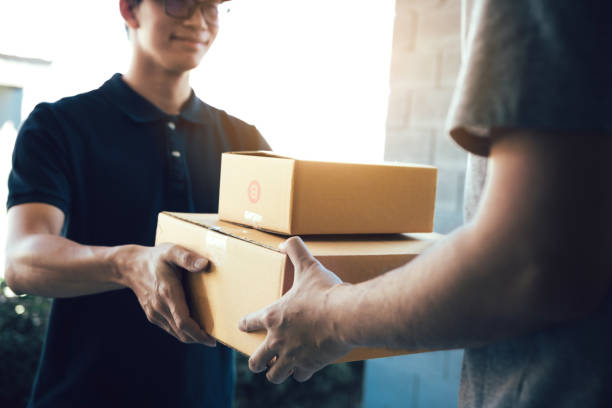 close up of hands cargo staff are delivering cardboard boxes with parcels inside to the recipient's hand. - entregar imagens e fotografias de stock