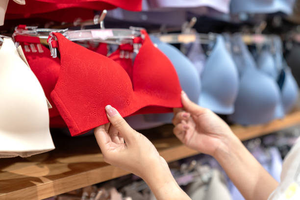 Close up of hands choosing bras cups size and looking light new wireless and seamless technology with red hot color and sexy bra in lingerie shop at department store. Woman shopping underwear concept. Close up of hands choosing bras cups size and looking light new wireless and seamless technology with red hot color and sexy bra in lingerie shop at department store. Woman shopping underwear concept. bra stock pictures, royalty-free photos & images