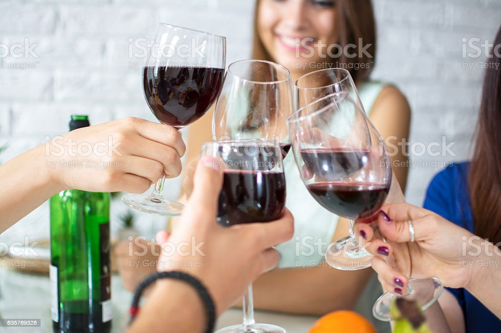Close up of hands clinking glasses with red wine. - foto de stock