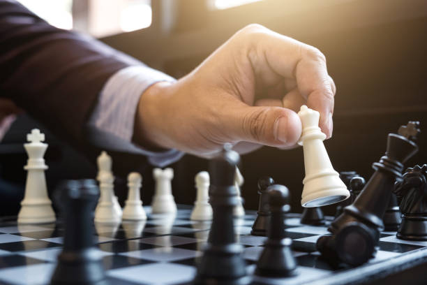 Close up of hands confident businessman colleagues playing chess game to development analysis new strategy plan, leader and teamwork concept for success. stock photo