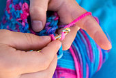 woman crocheting a pink girl dress with wool and hook.close up shot of professional crocheting woman.