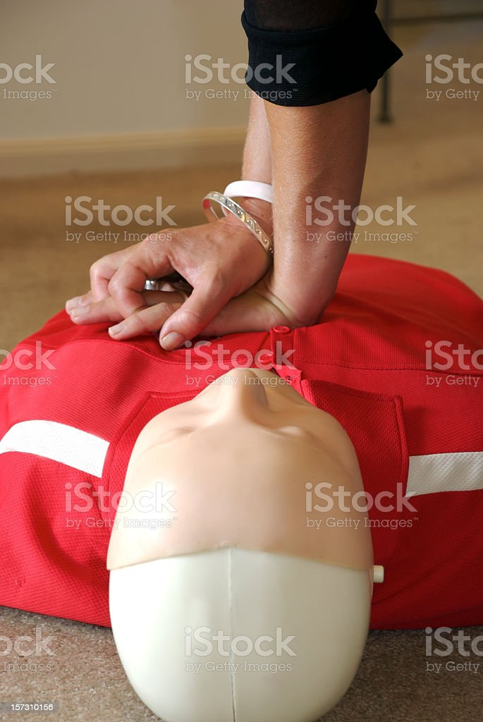 Close up of hands giving chest compressions to CPR dummy royalty-free stock photo