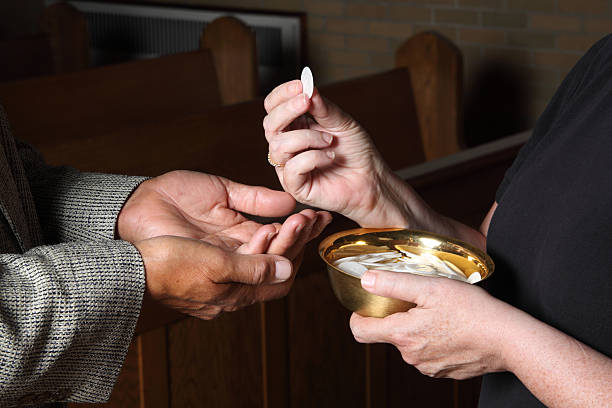close up of hands giving communion - communion stock photos and pictures