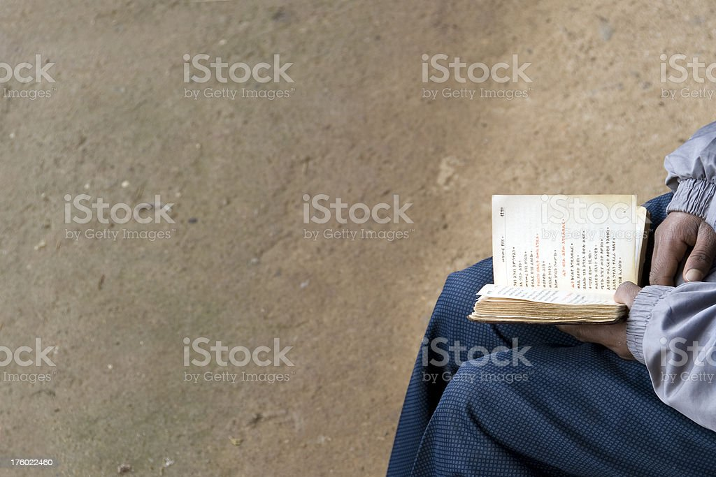 Close up of hands holding a bible in the amharic stock photo