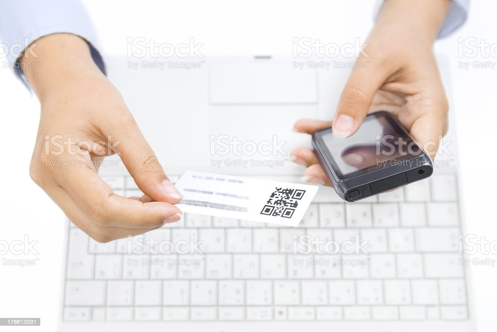 Close up of hands holding smart phone and business card stock photo