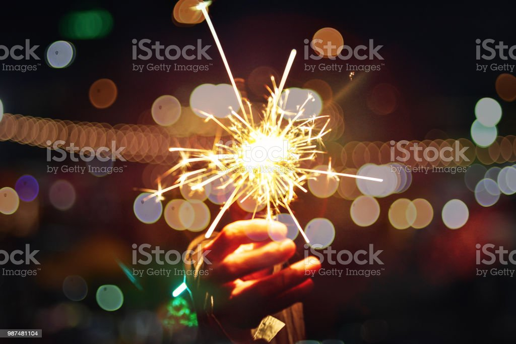 Close up of Hands Holding Sparklers At Night, Firework celebrate at night stock photo