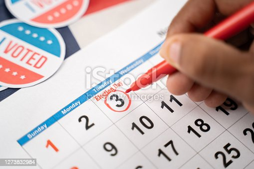 Close up of Hands marking November 3 election day on Calendar as reminder for voting - Concept of reminder for US election