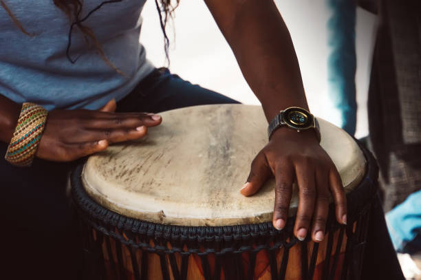 Close up of hands of a woman playing a drum. stock photo