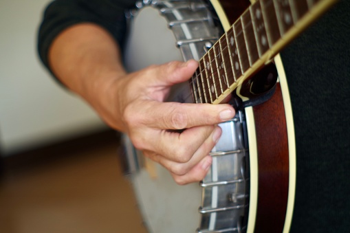 Close up of hands playing the banjo. The banjo is a stringed instrument with a thin membrane stretched over a frame or cavity to form a resonator. The membrane is typically circular, and usually made of plastic, or occasionally animal skin.