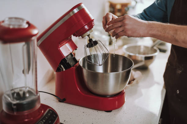 Close up of hands pouring egg into the bowl of mixer Modern red electric standing mixer with a big metal bowl and a man pouring raw egg into it electric mixer stock pictures, royalty-free photos & images