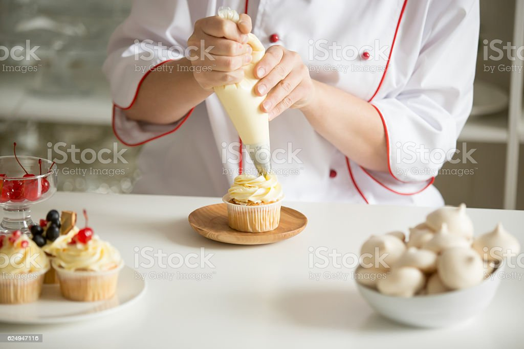 Close up of hands topping a cupcake with cream stock photo
