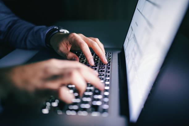 chiudi le mani digitando sul laptop. concetto di lavoro notturno. - protezione foto e immagini stock