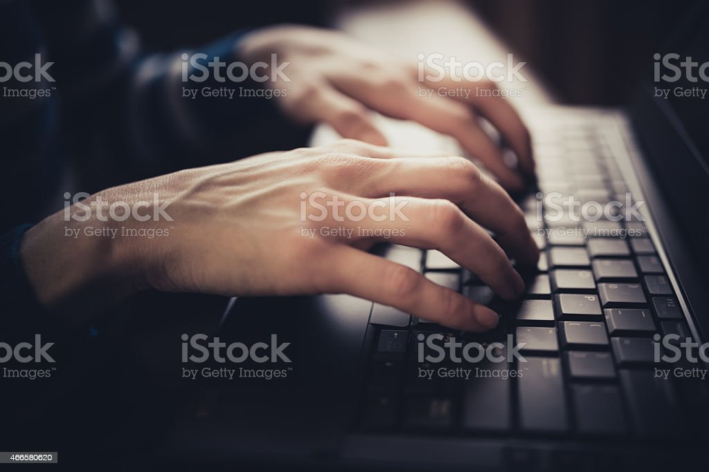 Close up of hands typing on laptop stock photo