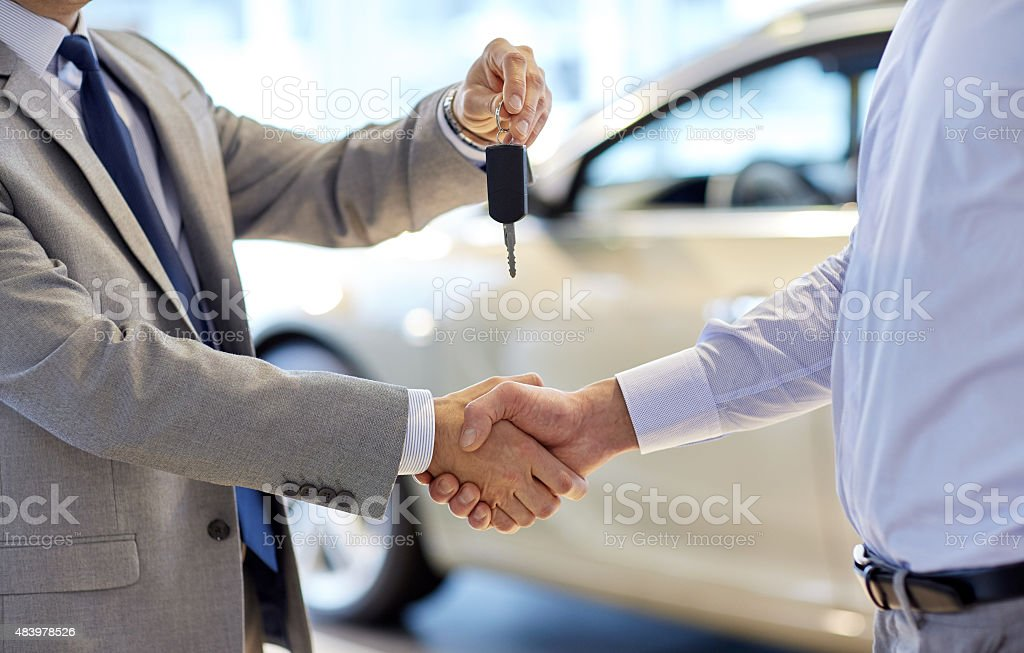 close up of handshake in auto show or salon auto business, car sale, deal, gesture and people concept - close up of dealer giving key to new owner and shaking hands in auto show or salon 2015 Stock Photo