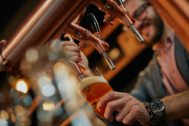 Close up of handsome caucasian bearded bartender standing in bar and pouring beer from tap. stock photo