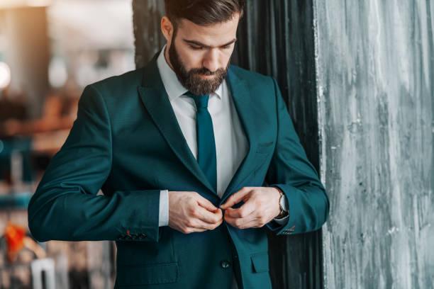 close up van knappe kaukasische zakenman van jas dichtknopen terwijl permanent buiten. - men blazer stockfoto's en -beelden