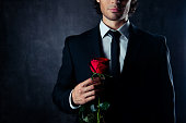 istock Close up of handsome young boyfriend holding red rose 947202270