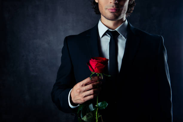 Close up of handsome young boyfriend holding red rose stock photo
