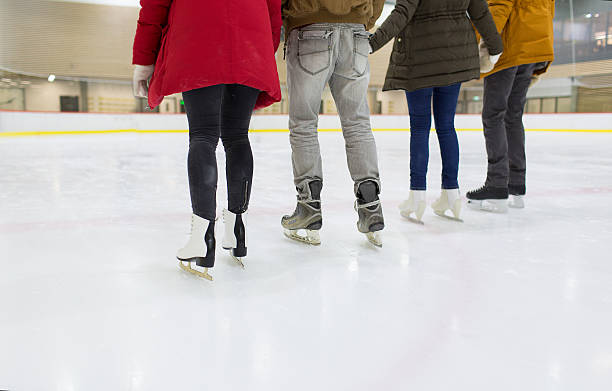 close up of happy friends skating on ice rink people, friendship, sport and leisure concept - close up of happy friends skating on ice rink ice skating stock pictures, royalty-free photos & images