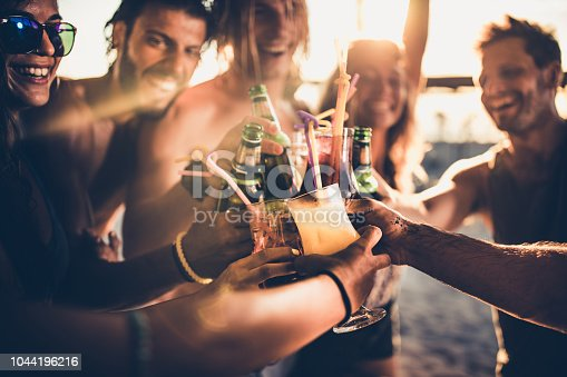 Close up of happy people having fun on a party while toasting with alcohol.
