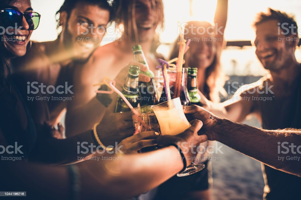 Close up of happy friends toasting with alcohol at sunset. stock photo