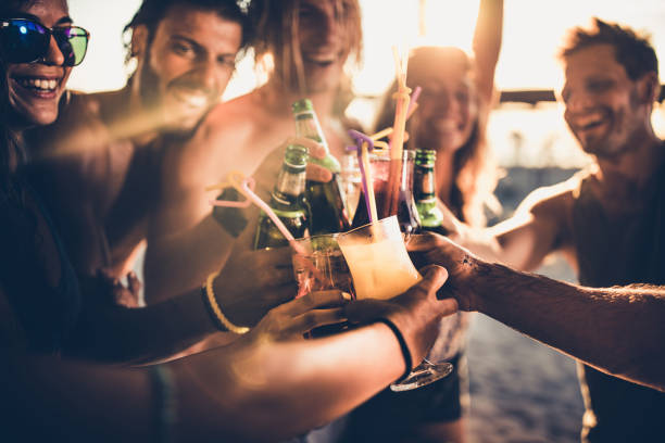 Close up of happy friends toasting with alcohol at sunset. Close up of happy people having fun on a party while toasting with alcohol. beer alcohol stock pictures, royalty-free photos & images