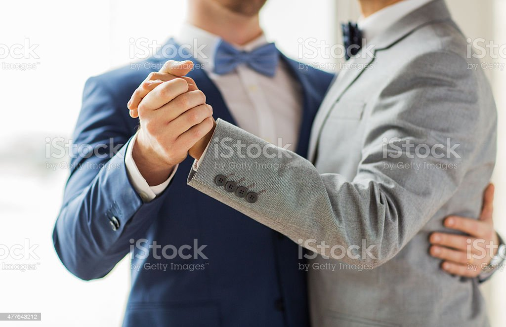 close up of happy male gay couple dancing stock photo