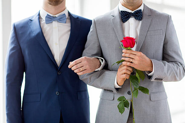 close up of happy male gay couple holding hands stock photo
