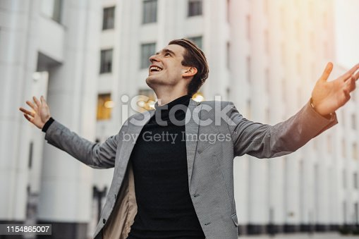Close up of happy man smiling and raising his arms to the sky while going to or from work. Concept of happy employee or dissmissed, fired or going on vacation worker.