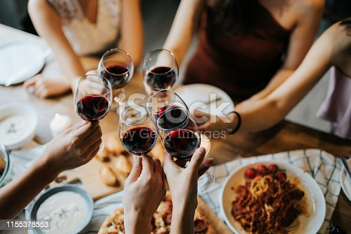 istock Close up of happy young friends having fun and toasting and celebrating with red wine during party 1155378553