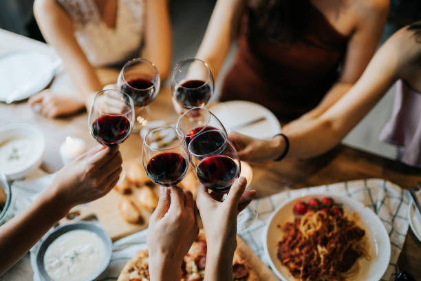 Close up of happy young friends having fun and toasting and celebrating with red wine during party Close up of happy young friends having fun and toasting and celebrating with red wine during party red wine stock pictures, royalty-free photos & images