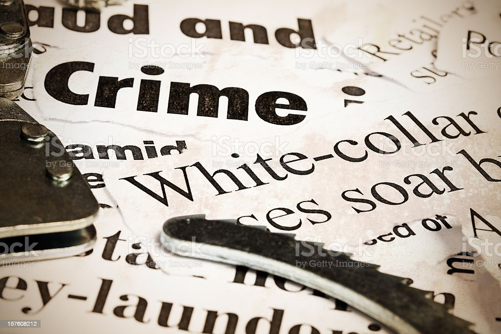 Close up of headlines on financial crime with handcuffs stock photo
