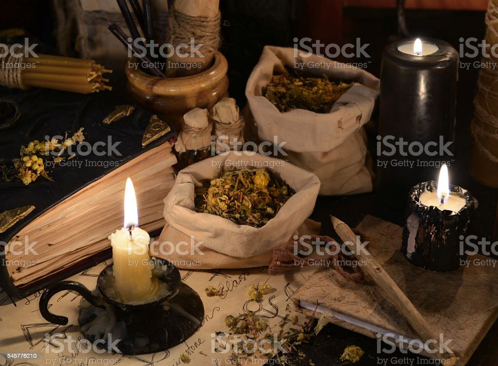 Close up of healing herbs, alchemy papers and burning candles stock photo