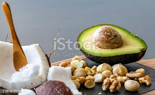 A close up of ketogenic food: coconut and coconut butter, avocado. walnuts and macadamia nuts
