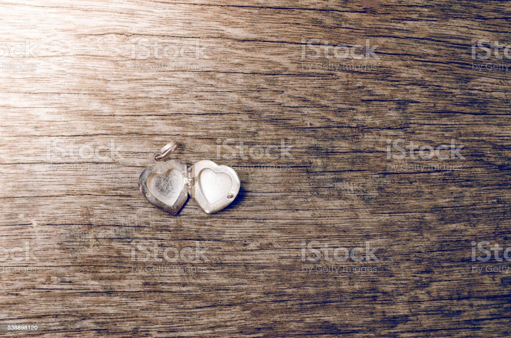 Close up of heart locket on wooden background stock photo