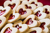 Close up macro image of heart-shaped cookies in a row. The middle of the cookies are filled with strawberry jam. Colour image with copy space.