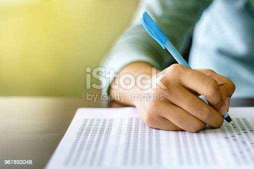istock Close up of high school or university student holding a pen writing on answer sheet paper in examination room. College students answering multiple choice questions test in testing room in university. 967893048