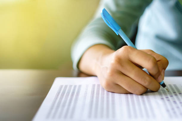 Close up of high school or university student holding a pen writing on answer sheet paper in examination room. College students answering multiple choice questions test in testing room in university. stock photo