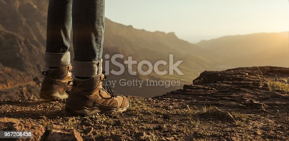 Close up of hikers boots enjoying the sunset on top of the mountain with copy space
