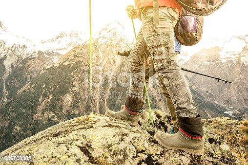 istock Close up of hikers trekking legs and boots on mountains 639708302