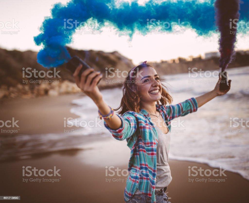 Primer plano de mujer hipster con bombas de humo en la playa - foto de stock