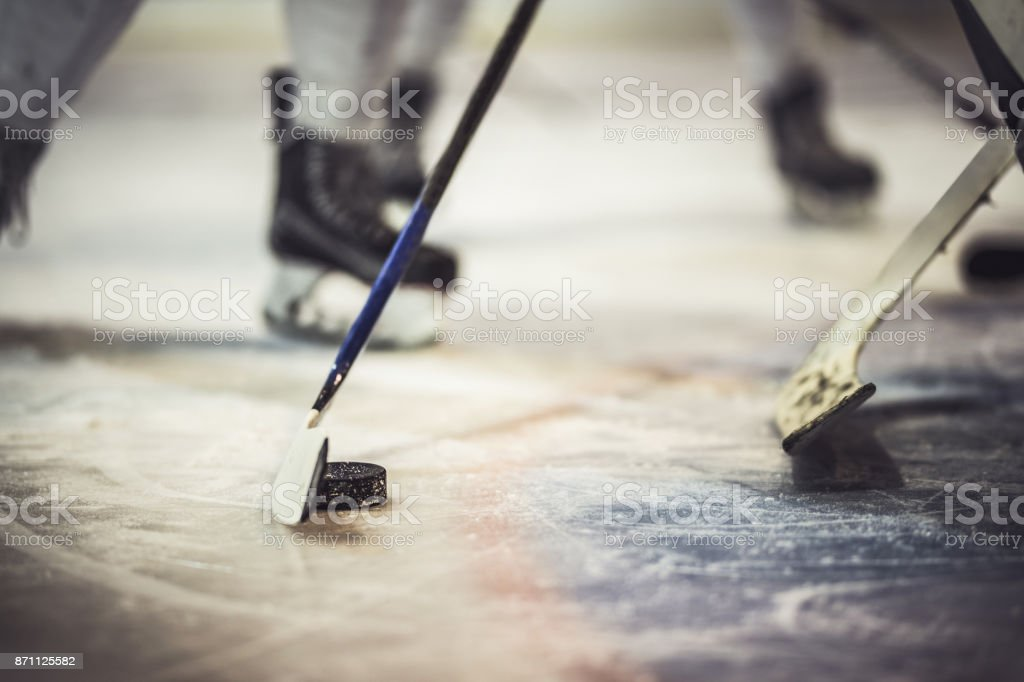 Close up of hockey puck and stick during the game. stock photo