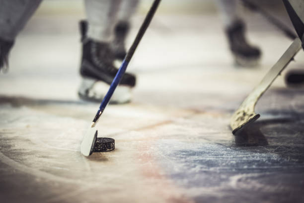close up of hockey puck and stick during the game. - hockey foto e immagini stock