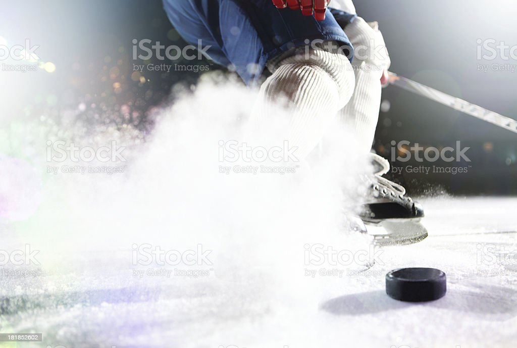 Close up of hockey puck with player in background stock photo