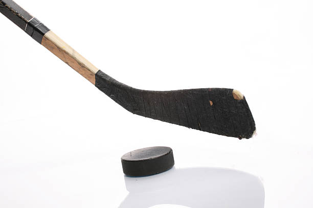 close up of hockey stick and puck on white background - hockey stick stock pictures, royalty-free photos & images