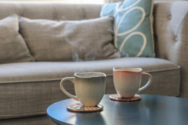 fermez-vous vers le haut des boissons chaudes avec la vapeur sur une table devant un sofa - tasse flat photos et images de collection