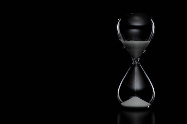 Close up of hourglass on black background. Close up of hourglass on black background. timer stock pictures, royalty-free photos & images