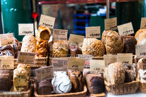 Close up color image depicting a large selection of artisan gourmet breads and pastries displayed on a bakery stall at a popular food market in London, UK, one of the most popular and oldest food markets in the world in fact. Each item is labelled and priced. Room for copy space.